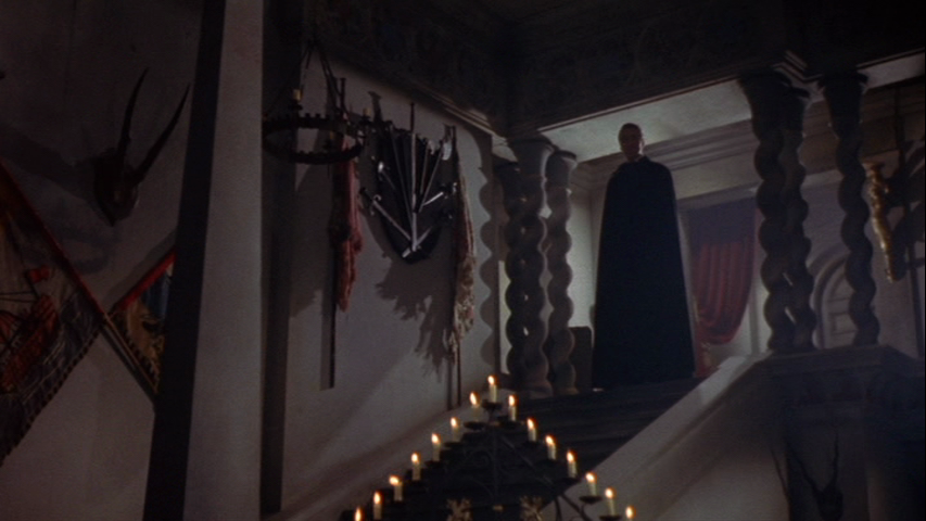 Dracula cuts an ominus silhouette from the top of the staircase. The use of light and shadows create an iconic image that pays tribute to earlier expressionist influences.