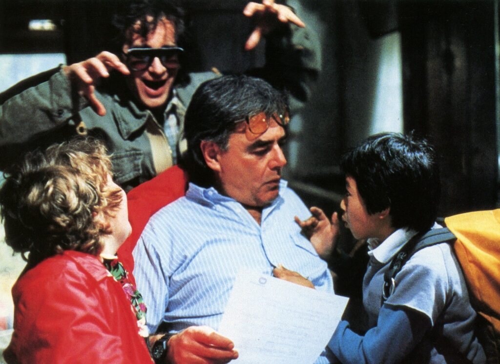 Richard Donner on the set of The Goonies (1985) with Executive Producer Steven Spielberg and actors  Jeff Cohen and Ke Huy Quan