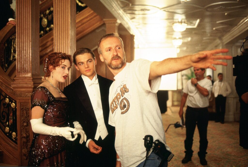 Kate Winslet and Leonardo Di Caprio take driection from James Cameron on the set of Titanic (1997)